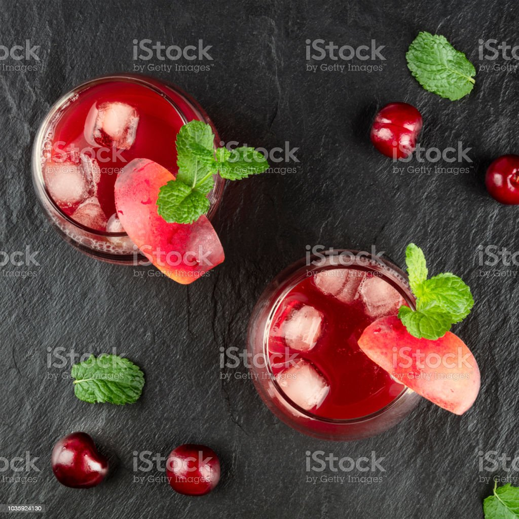 Overhead photo of vibrant red drink with cherries on black stock photo