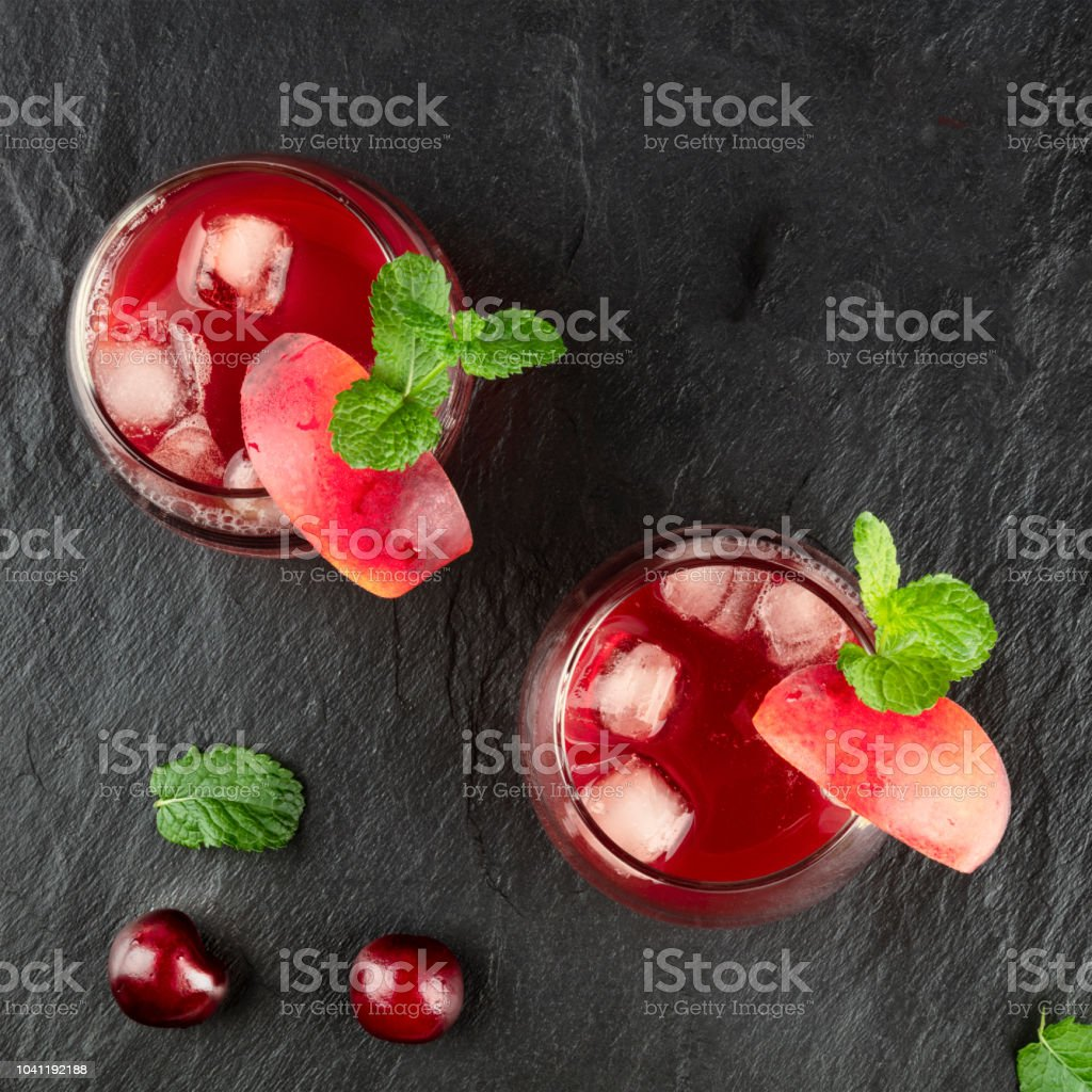 Overhead photo of vibrant red drinks with cherries on black stock photo