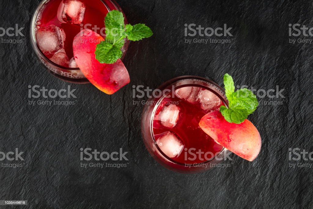 Overhead photo of vibrant red drinks with mint on black stock photo
