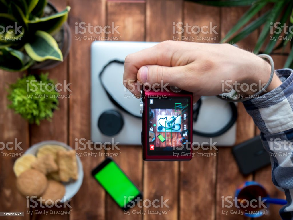 overhead photographer making photo with compact camera at home above the table zbiór zdjęć royalty-free