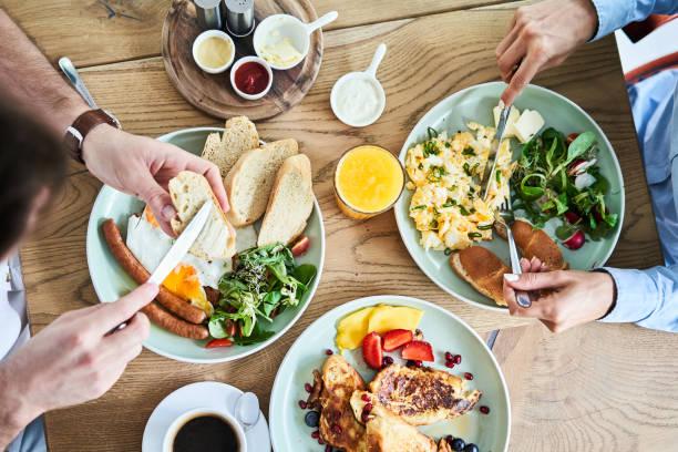 Oberbild von Ehepaar, das ein leckeres Frühstück im Restaurant isst – Foto