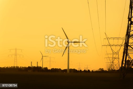 Overhead power lines in front of wind turbines and a power plant in the background during sunset.