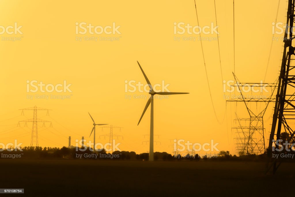 Overhead power line and wind turbines with a power plant stock photo