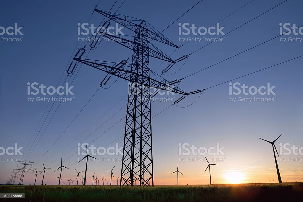 Overhead power line in front of wind turbines stock photo