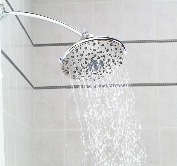 Overhead rainfall showerhead installed in ceramic tile shower  water wastage stock pictures, royalty-free photos & images