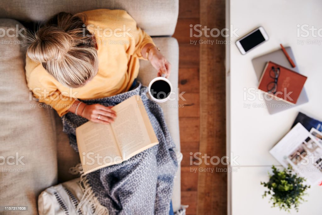 Overhead Shot Looking Down On Woman At Home Lying On Reading Book And Drinking Coffee - Royalty-free 30-39 Anos Foto de stock