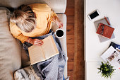 Overhead Shot Looking Down On Woman At Home Lying On Reading Book And Drinking Coffee