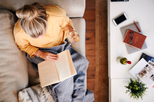 Overhead Shot Looking Down On Woman at Home lying on Reading Book and Drinking Wine - foto de stock