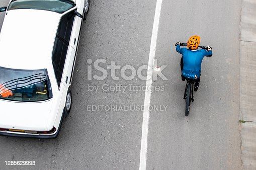 istock Overhead shot of  a cyclist being overtaken by a car on the road between Bogota and La Calera on the mountains in Colombia 1285629993