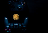 SHEFFIELD, UK - JUNE 2ND 2019: Overhead shot of a Microsoft black Xbox one controller and A Sony black Playstation 4 controller with a physical gold bitcoin in the middle of them both against a black background