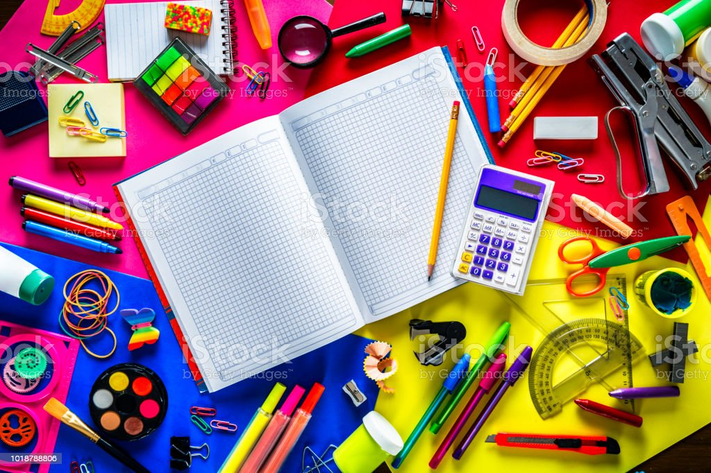 Overhead shot of back to school office supplies on multi colored background. Large group of objects. stock photo