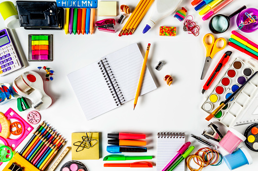 Back to school themes. Overhead shot of back to school office supplies on white background with paper note book into frame.