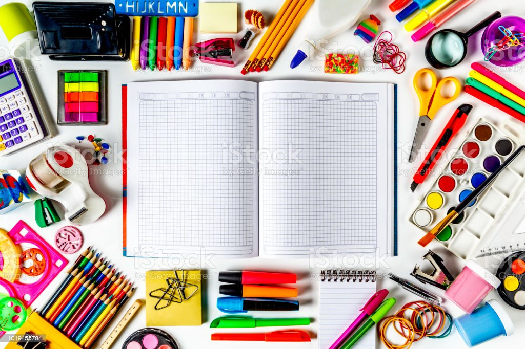 Overhead shot of back to school office supplies on white background with paper math note book into frame. stock photo