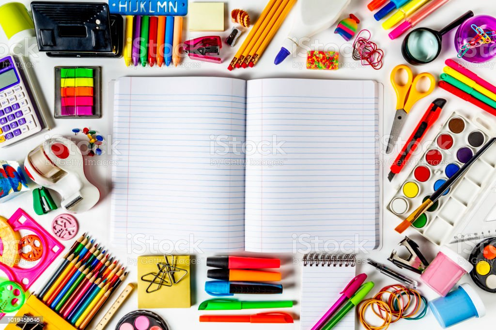 Overhead shot of back to school office supplies on white background with paper note book into frame. stock photo