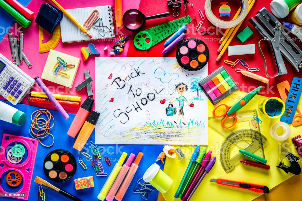 Overhead shot of back to school office supplies over a multi colored background. Child drawing into the frame. stock photo