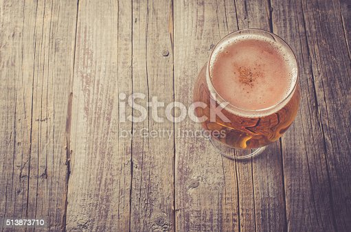 istock Overhead shot of beer glass on wooden table 513873710
