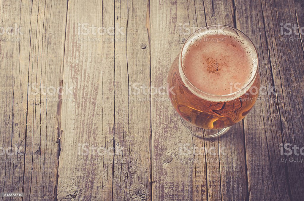 Overhead shot of beer glass on wooden table stock photo