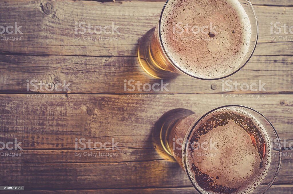 Overhead shot of beer glasses on wooden table stock photo