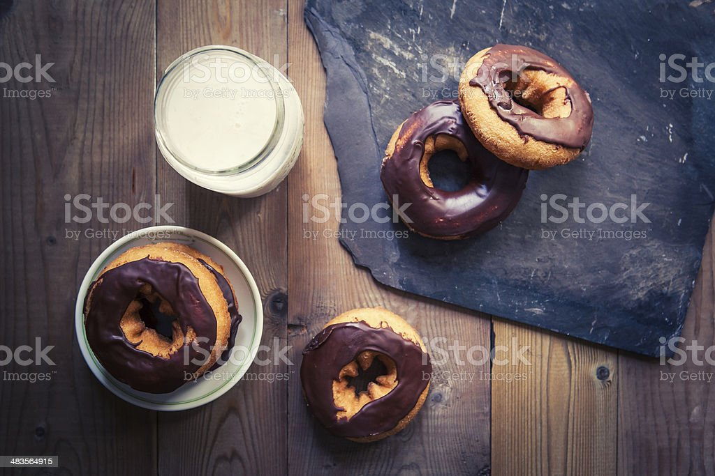 overhead shot of chocolate donuts and milk on slate and wood stock photo