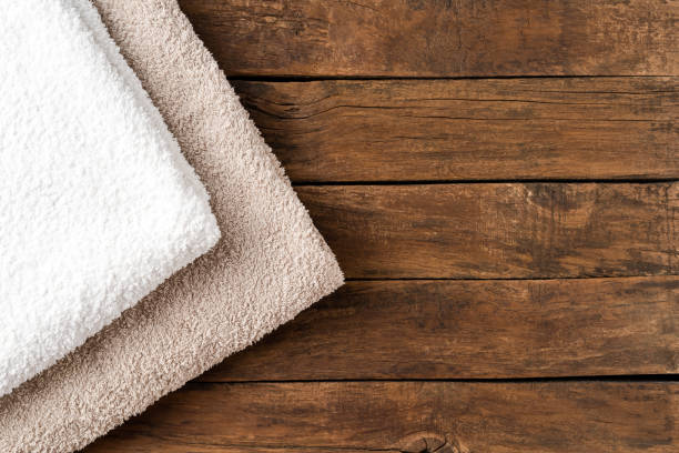 Overhead shot of clean folded towels on rustic wooden table with copyspace stock photo