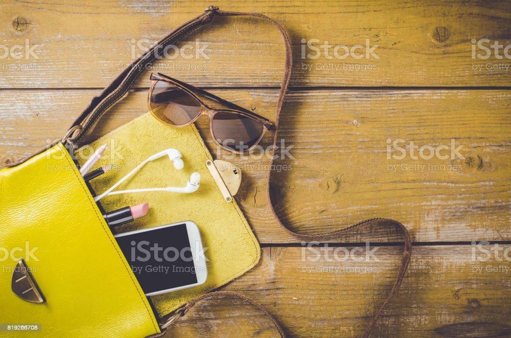 Tiro arriba del bolso femenino en una vieja mesa de madera - foto de stock