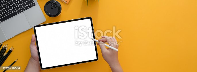 Overhead shot of freelancer writing on blank screen tablet with stylus on yellow worktable with supplies and copy space
