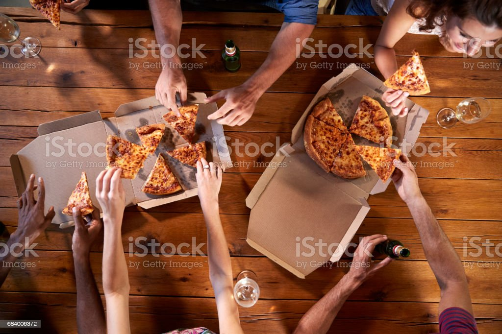 Overhead shot of friends at a table sharing take-away pizzas - foto de acervo