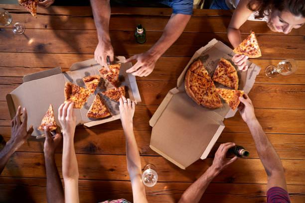 overhead skott av vänner vid ett bord dela take-away pizza - wine box bildbanksfoton och bilder