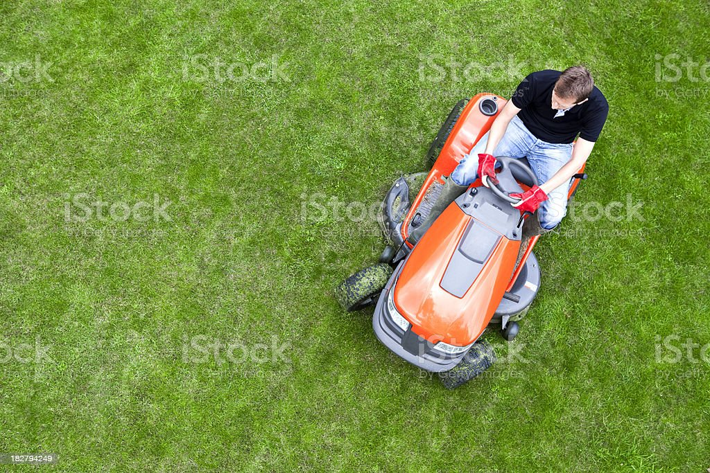 Overhead Shot of Gardener Mowing Lawn with Ride On Mower stock photo
