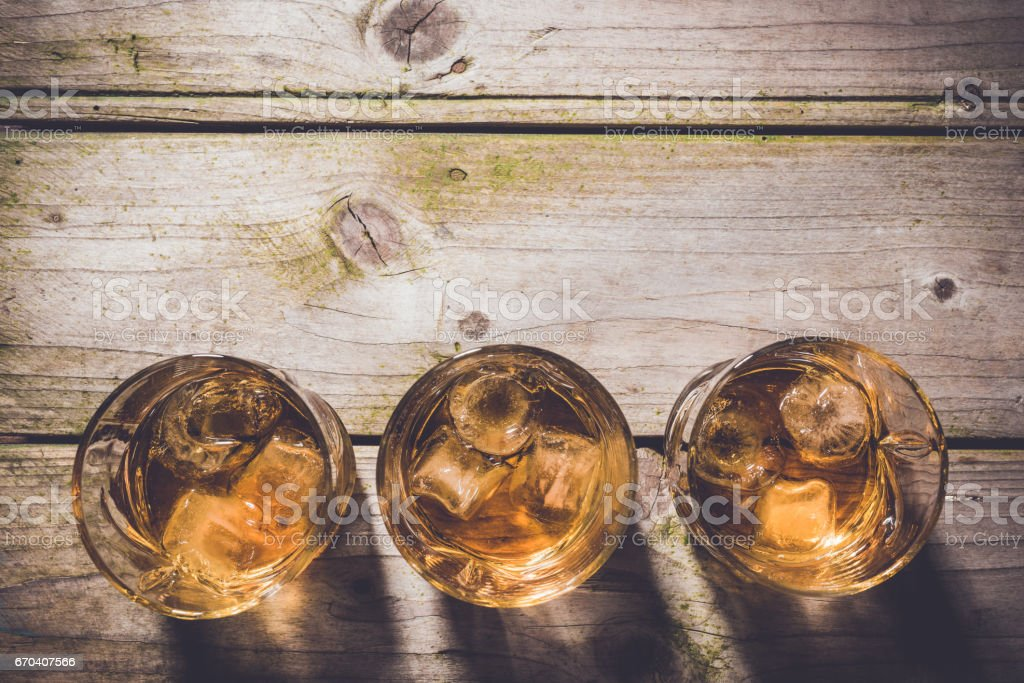 Overhead shot of glasses of whiskey on wooden table stock photo