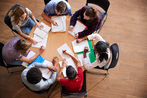 istock Overhead Shot Of High School Pupils In Group Study Around Tables 976330916