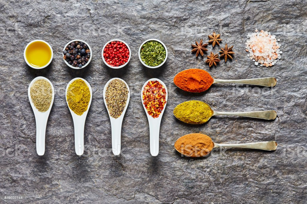 Overhead shot of Indian curry spices and herbs on slate stock photo