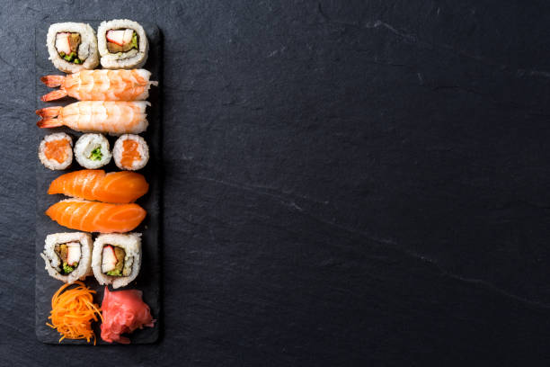 overhead shot of japanese sushi on black concrete background - japanese food stock photos and pictures