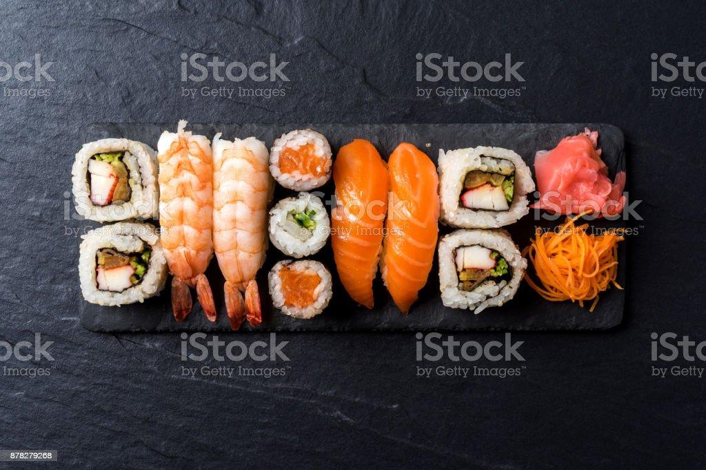 Overhead shot of Japanese sushi on black concrete background stock photo