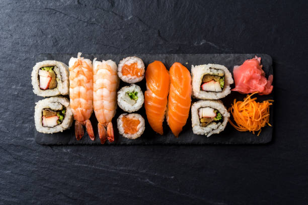 overhead shot of japanese sushi on black concrete background - sushi stock pictures, royalty-free photos & images