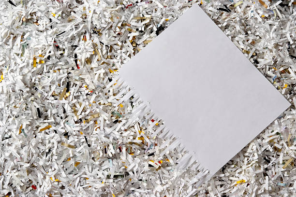 overhead shot of many shredded documents with blank paper - shredded paper stock photos and pictures
