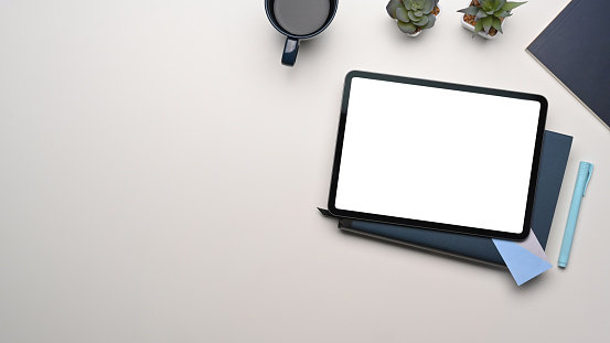 Overhead shot of mock up digital tablet with empty screen on whitetable. Blank screen for text message or information content.