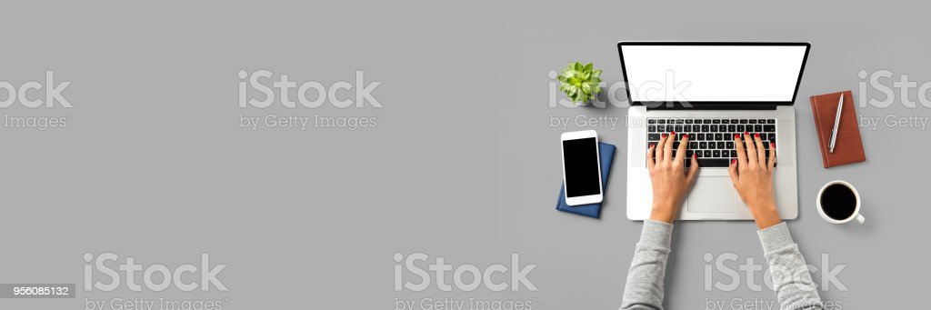Overhead shot of office desktop with female hands working on modern laptop stock photo
