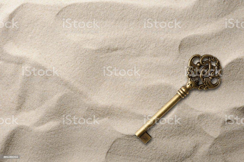 Overhead shot of old skeleton key on the sand stock photo