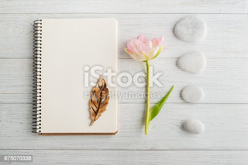 Overhead shot of pink tulip and pebbles over white wood table top with an open journal. Flat lay top view style.