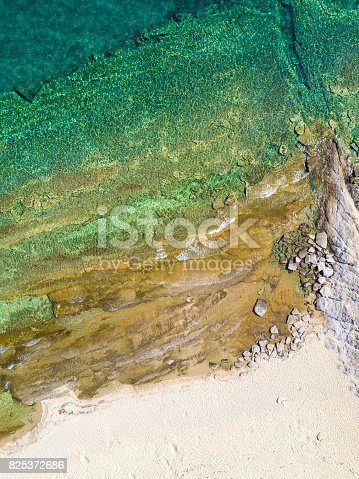 811600544 istock photo Overhead shot of sandy beach and turquoise sea 825372686