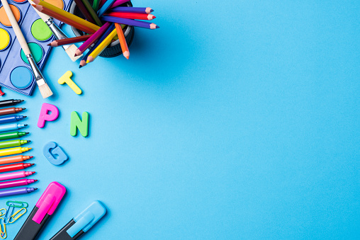 Overhead shot of school supplies on blue background. Close up