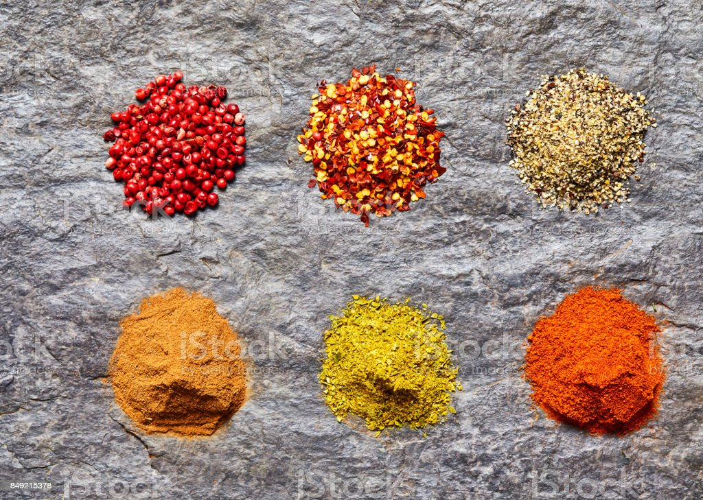 Overhead shot of spices collection on slate background stock photo