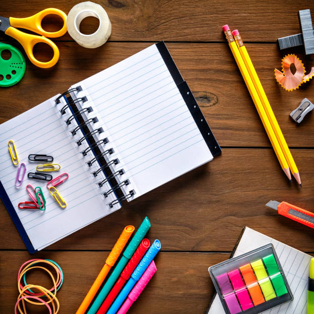 Overhead shot of stationery on wood desk with paper notepad and frame of school office supplies Back to school themes. Overhead shot of stationery on wood desk with paper notepad and frame of school office supplies stapler stock pictures, royalty-free photos & images