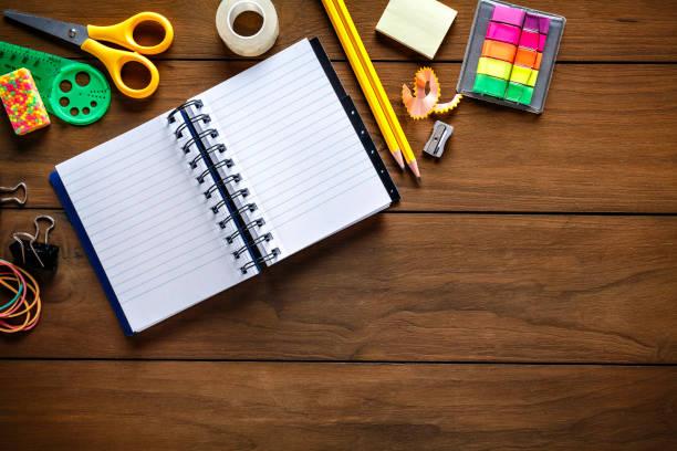 Prise de vue aérienne de papeterie sur le bureau en bois avec le bloc-notes en papier et le cadre des fournitures de bureau scolaire - Photo
