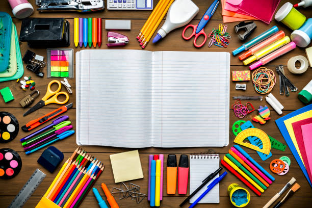 Overhead shot of stationery on wood desk with paper notepad and frame of school office supplies stock photo