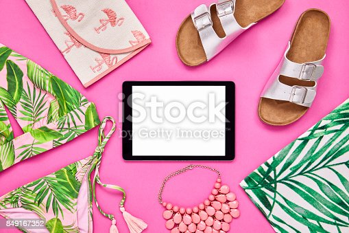 istock Overhead shot of tablet computer surrounded with summer vacation accessories 849167352