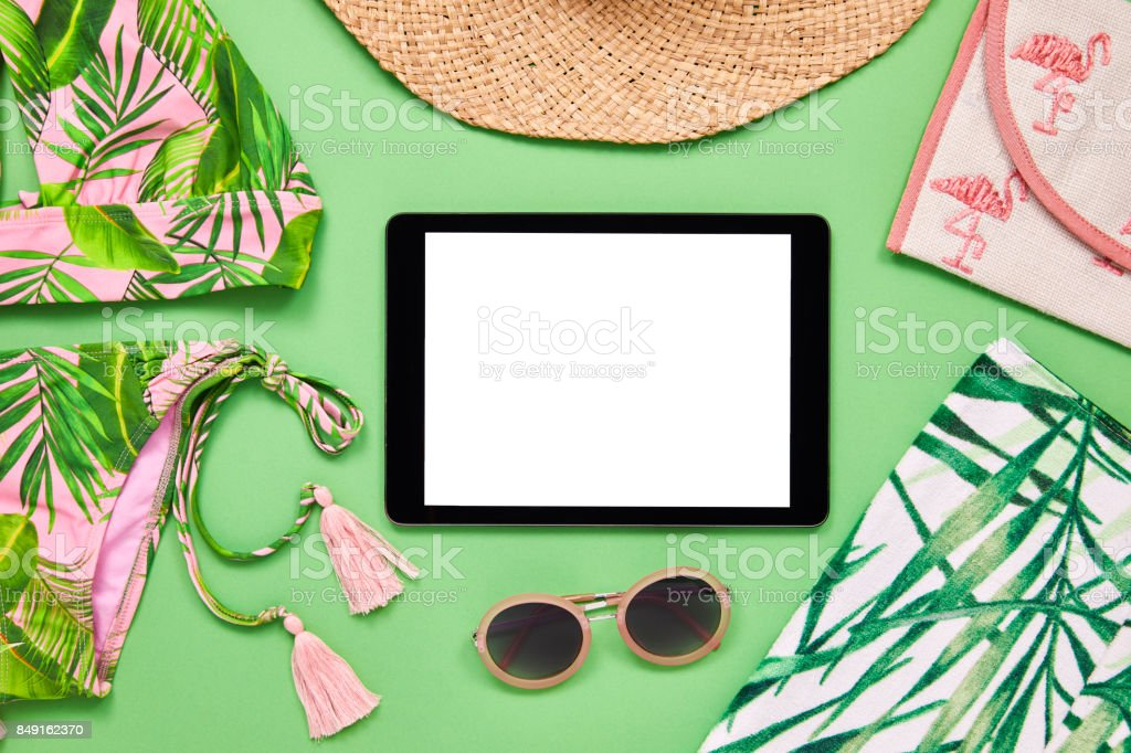 Flat lay of tablet computer with summer vacation accessories....