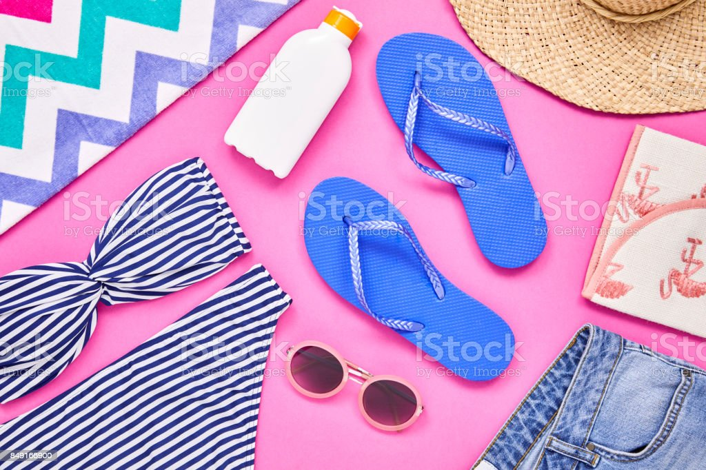 Overhead shot of travel and beach equipment on pink background stock photo