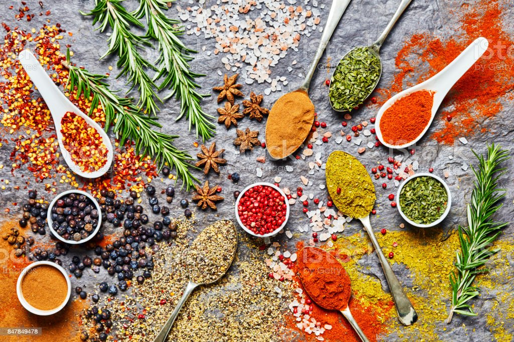 Overhead shot of various spices and herbs on slate background stock photo